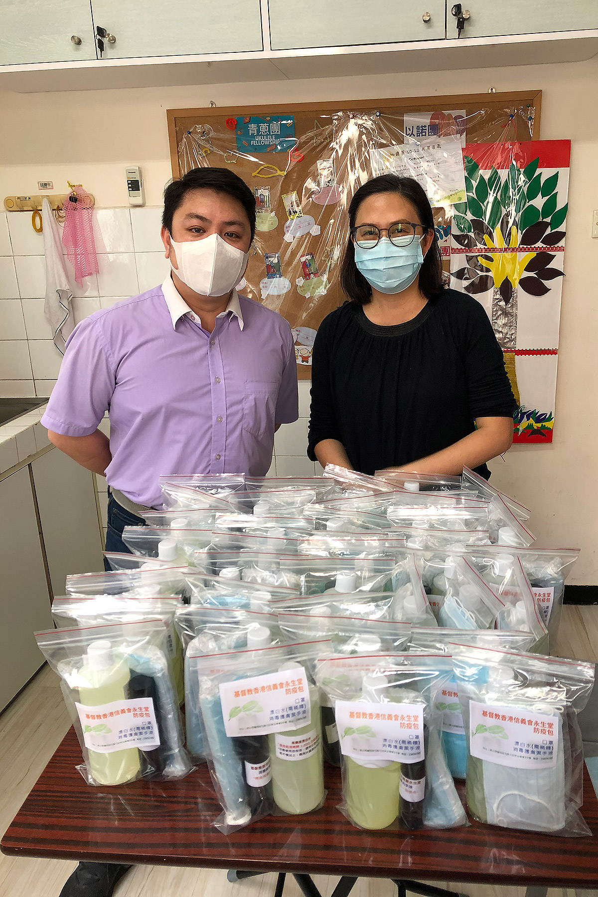 Rev. Ken Leung, pastor of the Eternal Life Lutheran Church, and a volunteer with supplies of hand sanitizer, masks and other hygiene products ready for distribution