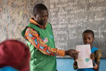 Painter and consulting artist Dogari Samson teaches children how to make drawings as a way to share messages of peace. All photos: LWF/Albin Hillert