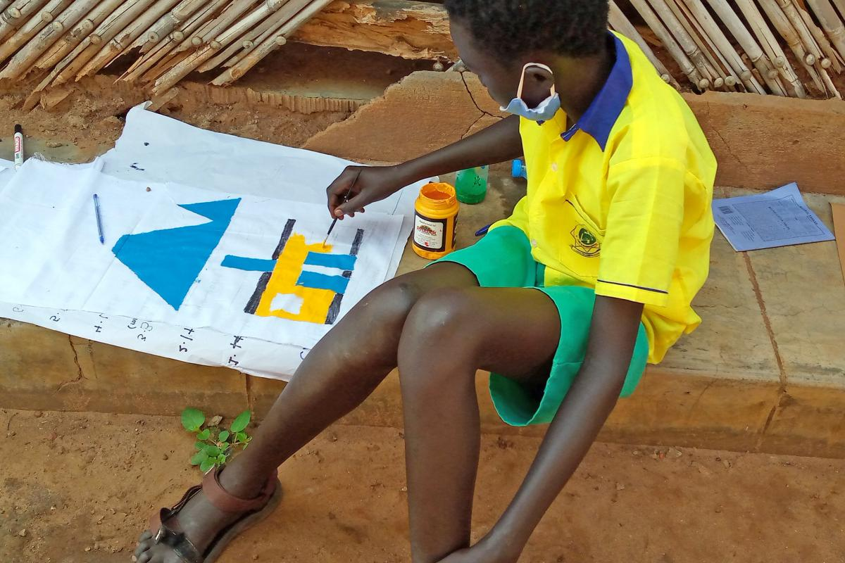A young refugee paints a house during the retreat. Photo: LWF/ H. Lehto